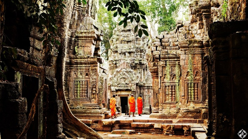 Monks wandering through temple ruins of Ta Prohm.