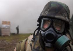 A sailor from the Naval Mobile Construction Battalion (NMCB) 11, adjusts his Mission Oriented Protective Posture (MOPP) gear during a simulated chemical agent attack during a field training exercise in 2008. U.S. Navy Photo