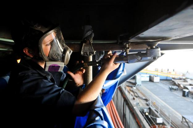 A sailor removes deteriorated paint and rust with a disc sander on a weather deck aboard the aircraft carrier USS Ronald Reagan on Sept. 6, 2012. U.S. Navy Photo