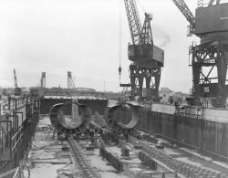 Pressure-hull sections in a submarine basin at the Portsmouth Navy Yard in March 1943. The shipyard had developed and refined sectional construction in the years leading up to World War II, and when war came the yard was poised to capitalize on a sudden surge in demand and the need for mass-production methods, University of New Hampshire Library.