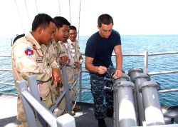 Royal Cambodian Navy sailors observe U.S. Navy Intelligence Specialist 3rd class Sean Tiberia perform daily maintenance on the Mark 53 decoy launching system aboard the USS Vandegrift (FFG 48) in October 2012. U.S. Navy Photo