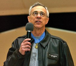 Jack Jacobs, retired U.S. Army colonel and Medal of Honor recipient, adresses forward deployed troops at a USO event in 2005. US Air Force Photo