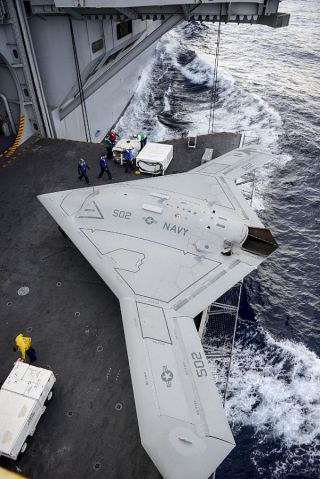 An X-47B Unmanned Combat Air System (UCAS) demonstrator aircraft is transported  on an aircraft elevator aboard the aircraft carrier Harry S. Truman (CVN-75). US Navy Photo
