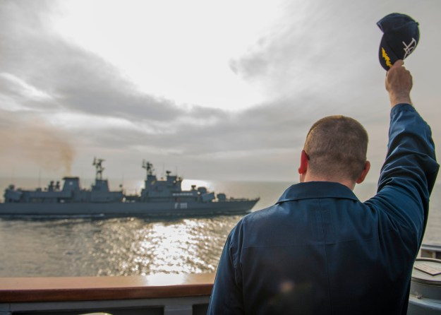 Cmdr. Scott Jones, commanding officer of the Arleigh Burke-class guided-missile destroyer USS Donald Cook (DDG 75) waves to the Romanian navy frigate ROS Marasesti (F 111) on April 23, 2014. US Navy Photo