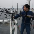 Amy Sun, an advanced program lead for Lockheed-Martin, adjusts a UHF antenna aboard USCGC Healy (WAGB-20) while underway near Alaska on Aug. 10, 2014.