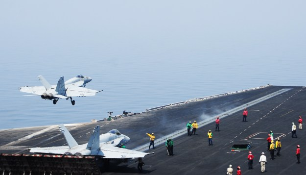 Sailors direct aircraft as an F/A-18E Super Hornet attached to the Tomcatters of Strike Fighter Squadron (VFA) 31 takes off from the flight deck of the aircraft carrier USS George H.W. Bush (CVN-77). US Navy Photo