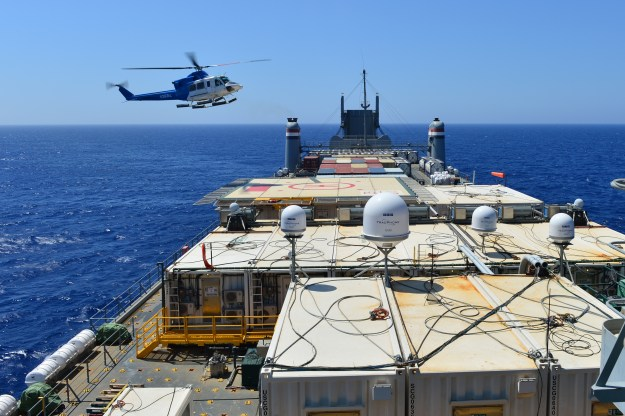 A helicopter approaches the container ship MV Cape Ray (T-AKR 9679) in the Mediterranean Sea to drop off cargo Aug. 4, 2014. US Navy Photo