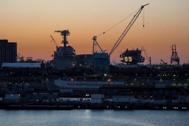 Thw aircraft carrier Gerald R Ford (CVN-78) and Enterprise (CVN-65) sit side by side in the South Yard as the sunrise starts to light up the sky. HII Photo