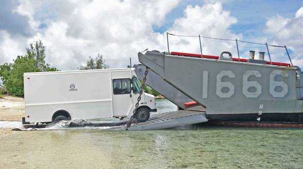 A civilian power generating truck is driven from a Guam beach onto the deck of Landing Craft Utility (LCU) 1666, attached to Naval Beach Unit (NBU) 7, for disaster relief efforts in Saipan after Typhoon Soudelor. US Navy photo via US Naval Base Guam Facebook page.
