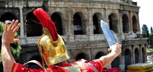 A man dressed as a Roman centurion and who earn his living by posing with tourists speaks to a colleague standing on the Colosseum during a protest on April 12, 2012 in Rome. The costumed centurions are asking for the right to work there after they were banned following a decision by local authorities. AFP PHOTO / ALBERTO PIZZOLI (Photo credit should read ALBERTO PIZZOLI/AFP/Getty Images)