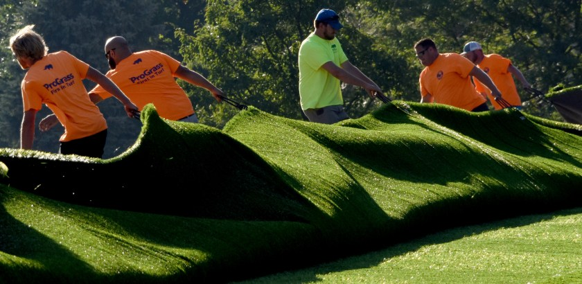 "Darrell Sapp/Post-Gazette / Pittsburgh — 09/13/2016 — for Local— STAND ALONE — Going Green in Pleasant Hills— A crew with ""Pro Grass"" pull a newly stiched strip of synthetic turf to make up part of a new athelic field near the Pleasant Hills muncipal building.   digital image #dsc_7876             slug —  20160914dsGoingGreenLocal02.jpg"