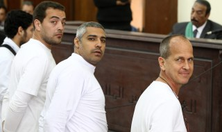 epaselect epa04148406 Australian journalist Peter Greste (R) and other co-defendants stand in front of the judge's bench during their trial for allegedly supporting a terrorist group and spreading false information, in Cairo, Egypt, 31 March 2014. Judge Mohammed Nagui, who is trying three Al-Jazeera journalists and five co-defendants on terror charges in Egypt, called them out of the defendant's cage on 31 March 2014 to hear individual requests. The trial was adjourned until 10 April. A total of 20 defendants in the case are charged with harming Egypt's national interests by spreading false news and assisting or belonging to a terrorist organization, but 12 are being tried in absentia.  EPA/KHALED ELFIQI