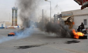 A picture taken on May 11, 2016 in the Tunisian southern border town of Ben Guerdane, shows tires burning on a street as the town went on strike in protest at a decision by Libyan authorities late last month to halt cross-border trade on which its economy depends. Ben Guerdane is one of the North African nation's poorest towns and has also been hit by jihadist violence from across the border that killed seven civilians and 13 security personnel in March as well as 55 extremists. Only the hospital emergency department, a pharmacy and some schools remained open./ AFP PHOTO / FATHI NASRI