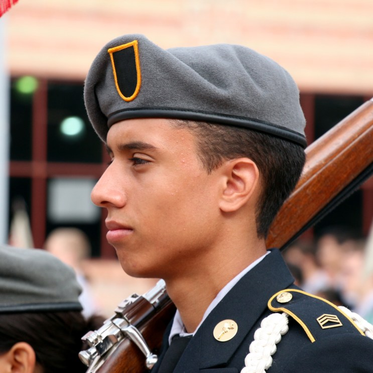 Eric Mendez stands at attention listening to Col. Ricardo Morales's speech.