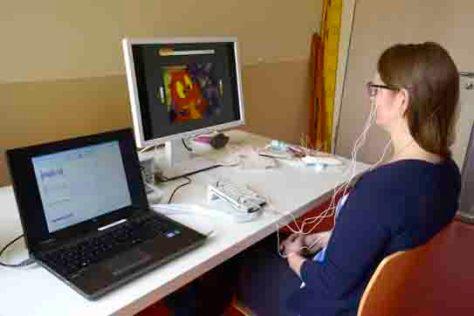 Ein Elektroencephalogramm (EEG) misst die Hirnströme einer Patientin beim Training und gibt sofortige Rückmeldung zum Maß ihrer Konzentration über einen Bildschirm.