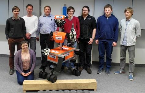 """Die Arbeitsgruppe Autonome Intelligente Systeme um Prof. Dr. Sven Behnke (hinten, Dritter von links) vom Institut für Informatik VI der Universität Bonn hat viel Erfahrung mit der Entwicklung von Robotern wie """"Momaro"""" und schon mehrere internationale Wettbewerbe gewonnen. © Foto: Universität Bonn"""