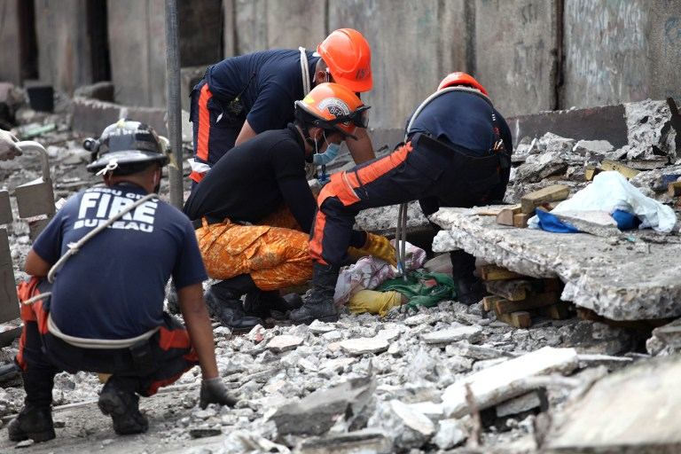 Rescuers try to uncover an unidentified man under slabs of cement in Cebu City, Philippines after a major 7.1 magnitude earthquake struck the region on October 15, 2013.  At least 20 people were killed on October 15 when the earthquake tore down buildings across three islands that are among the Philippines' most popular tourist attractions, authorities said. AFP PHOTO / Chester Baldicanto
