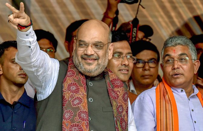 Kolkata: BJP National President Amit Shah flashes the victory sign as West Bengal BJP President Dilip Ghosh (R) looks on, during a public rally in Kolkata on Saturday, August 11, 2018. (PTI Photo/Swapan Mahapatra)   (PTI8_11_2018_000109B)