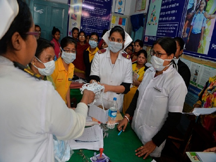 Nurses and medical staff distribute protective facemasks to patients coming to the outdoor patient department (OPD) for an awareness event about the COVID-19 coronavirus and other airborne diseases at the Siliguri District Government hospital in Siliguri on February 21, 2020. (Photo by DIPTENDU DUTTA / AFP) (Photo by DIPTENDU DUTTA/AFP via Getty Images)
