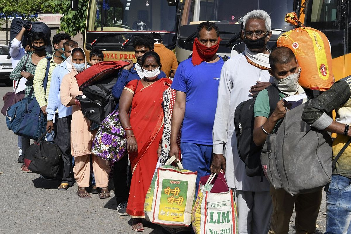 Stranded migrant workers and their families queue as they wait for a medical screening before going to a railway station and board on a special train to Raebareli in Uttar Pradesh state after the government eased a nationwide lockdown imposed as a preventive measure against the COVID-19 coronavirus, at the Guru Nanak Auditorium, in Amritsar on May 18, 2020. (Photo by NARINDER NANU / AFP)