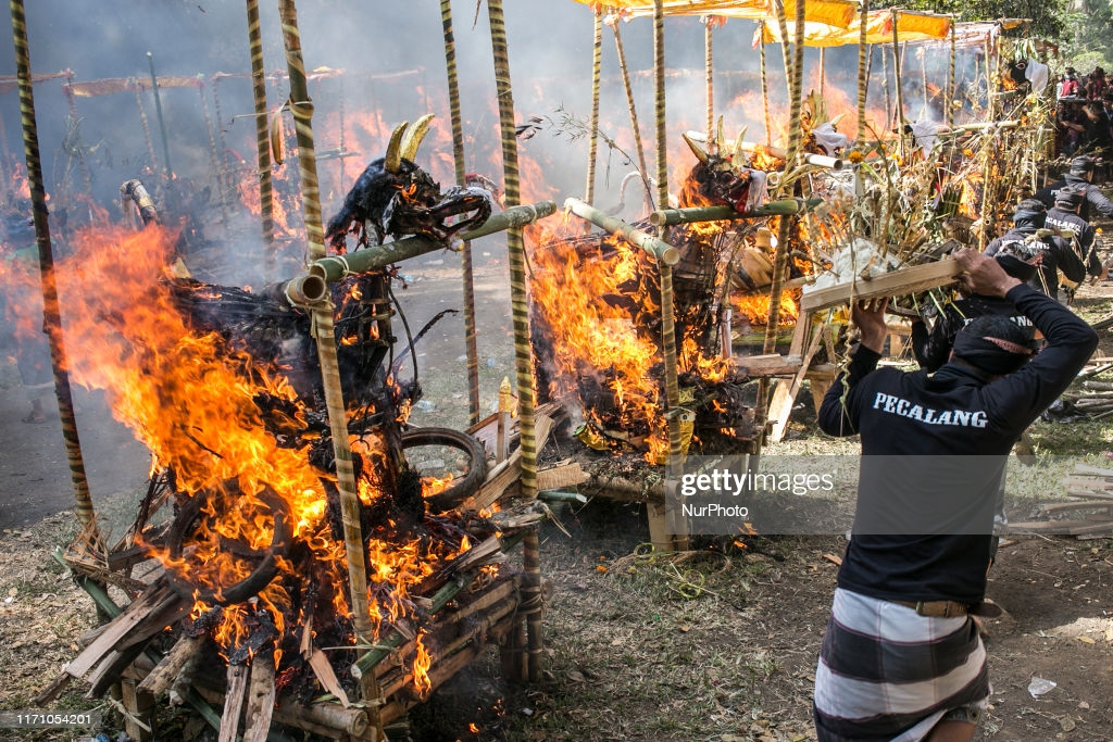 Coffin in shape of mythical dragon and bull being burnt during mass cremation or locally called Ngaben rituals in the grave yard of Bayad Village in Tegallalang, Gianyar, Bali on September 25, 2019. A total of 59 bodies in the form of human skeletons that died several years ago were cremated simultaneously in order to ease the cost of the ceremony for local residents. (Photo by Johanes Christo/NurPhoto via Getty Images)