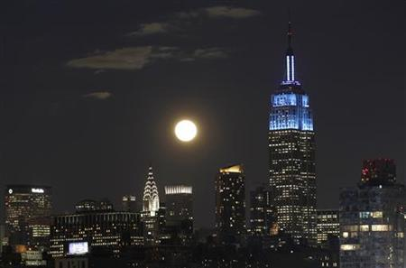 A full moon rises over the skyline of Manhattan between the Chrysler Building and the Empire State Building in New York