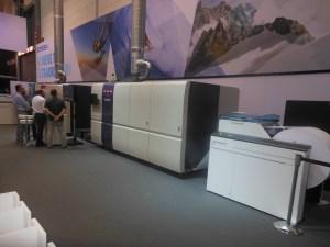 SCREENグラフィックアンドプレシジョンソリューションズ ロール式高速インクジェット印刷機の最新鋭機種「Truepress Jet520HD」を出展。オフセット印刷用のコート紙にアンカー剤などを使わずに印刷ができる新インクを開発。一般コート紙や普通紙にも印刷でき、さらにオフセット印刷レベルの耐擦過性を実現し、用紙の風合いを活かした印刷が可能