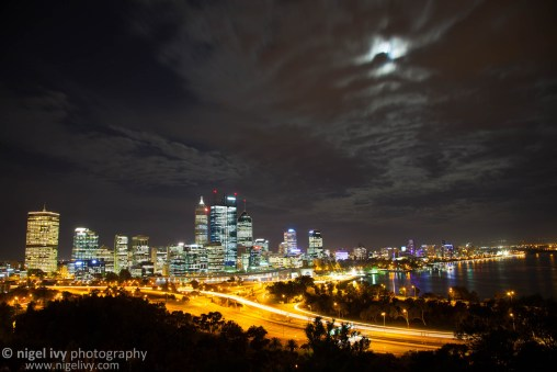 Last week, while we were in Perth, we visiting Kings Park one evening. If you ever go to Perth, Kings Park is well worth a visit! It has a great view of the city and Swan River.  Here's a shot I got of the city lights. It was the day before full moon, so the moon was quite bright by then, but unfortunately there were a lot of clouds in the sky. It still came out nicely.