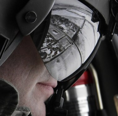 The Red River flooding is reflected in the visor of Sgt. First Class Todd Sudheimer with the Minnesota National Guard in St. Paul as he looks out of his UH-60 Blackhawk helicopter south of Fargo Sunday. (AP Photo/Charles Rex Arbogast)