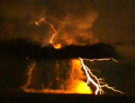 Lightning flashes in a roiling cloud of ash over Mt. Redoubt on March 27th. Particles of ash rubbing together in the cloud (like socks rubbing against carpet) are partly responsible for the buildup of electrostatic charge. Photo credit and copyright: Bretwood Higman, Ground Truth Trekking. [click for more]