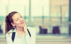 37960925 - portrait happy young woman thinking dreaming has many ideas looking up isolated office windows background. positive human face expression emotion feeling reaction. decision making process concept