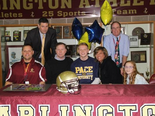 Brandon Tobin signing his national letter of intent to play football at Pace University in March 2014. (Courtesy of Arlington High School Athletics)