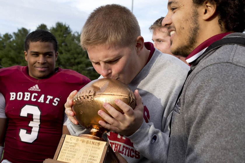 Slotback Tyler Janssen '17 lays a tender kiss on the CBB trophy. (Courtesy of Phyllis Graber Jensen/Bates College)