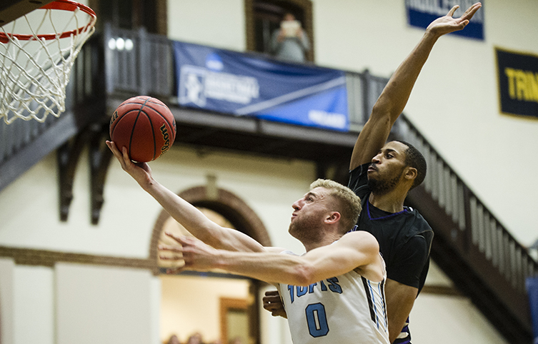 Tufts guard Ben Engvall '18 lays the ball in as Amherst's David George '17 tries for a swat from behind (Courtesy of Tufts Athletics).