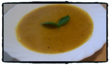 Thai Yellow Soup garnished with a sprig of basil and a dash of truffle oil