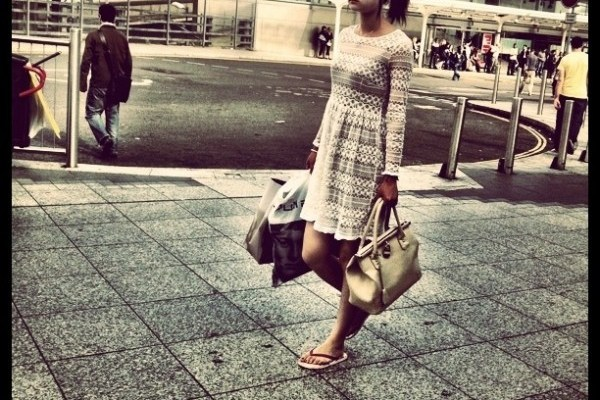 Fabulously trendy girl in a cream lace long-sleeve dress and cream bag near Shepherd's Bush