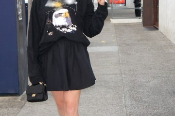 Gretchen Hackmann of Nubry wearing a bald eagle Topman sweatshirt with an A-line skirt by Ashlee Brooks, Giuseppe Zanotti glitter pumps, and top-knot Bun