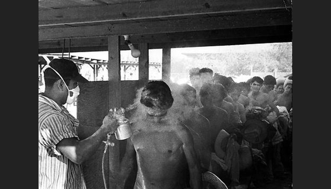 """""""Bracero workers being fumigated,"""" 1956. Photograph by Leonard Nadel, NMAH, History of Technology Collections."""