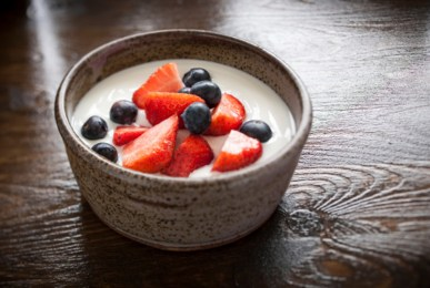 A rustic bowl of natural yogurt with fresh fruit