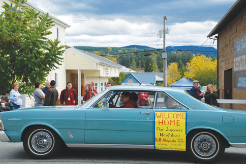 """Bill Akiyoshi and his wife, Ruth, rode in the parade at Eatonville's centenary. Their car said, """"Welcome Home, Our Japanese Neighbors."""""""