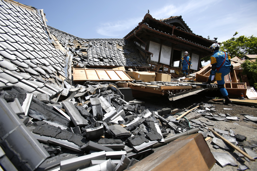 Police rescue team members search through damaged houses to check possibility of trapped people in southern Japan on April 15. (AP Photo/Koji Ueda)