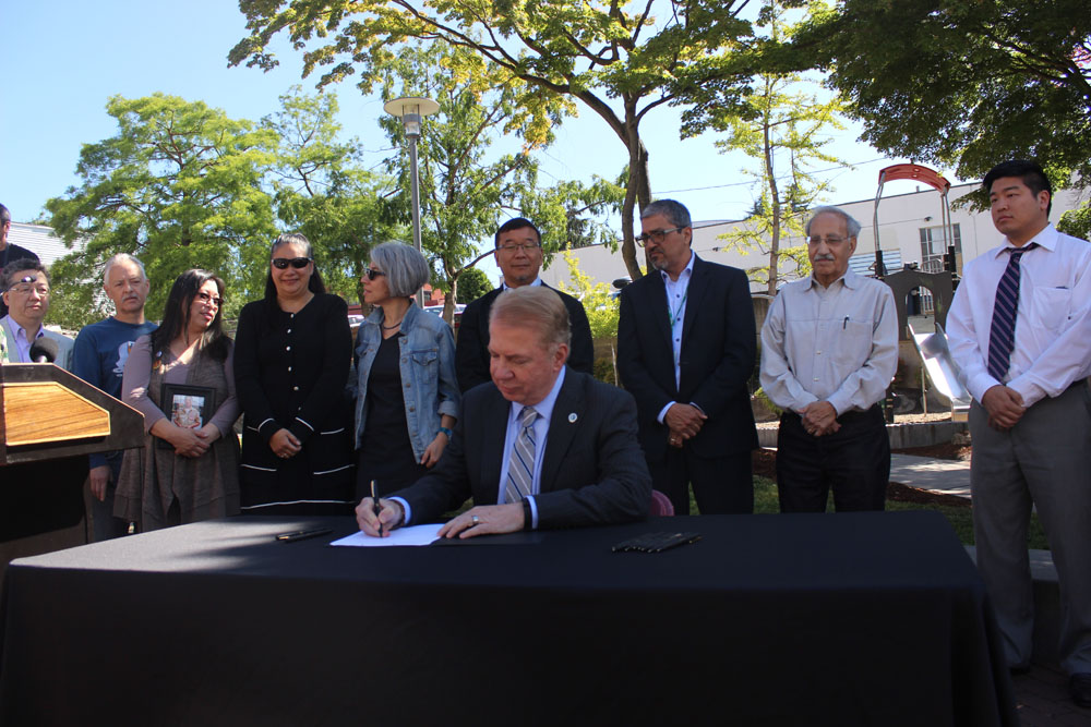 Mayor Ed Murray signing a resolution naming Donnie Chin International Children's Park. (Photo provided by the City of Seattle)
