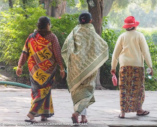 Women wearing batik block prints Malaysia walk along the garden path.