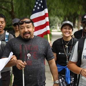 MERCEDES HERNANDEZ, EMILIANO LEONIDES, FELIPE TOVAR, LILY NGUYEN-ELLIS (CARRYING THE U.S. FLAG) AND YOUNG BRIAN TOVAR WERE PART OF A GROUP OF PILGRIMS WHO WALKED 50 MILES FROM SANTIAGO DE COMPOSTELA CHURCH IN LAKE FOREST TO THE CATHEDRAL OF OUR LADY OF THE ANGELS, ASKING FOR IMMIGRATION REFORM.