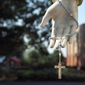 A ROSARY HANGS FROM A STATUE OF JESUS AT THE SHRINE OF OUR LADY OF MARTYRS IN AURIESVILLE, N.Y. CNS/NANCY WIECHEC