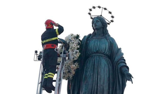 A FIREFIGHTER SALUTES AFTER PLACING A WREATH ON A STATUE OF MARY OVERLOOKING THE SPANISH STEPS IN ROME DEC. 8, THE FEAST OF THE IMMACULATE CONCEPTION. ROME'S FIREFIGHTERS HAVE OBSERVED THE TRADITION EVERY YEAR SINCE 1857. / PHOTO (CNS PHOTO/PAUL HARING)
