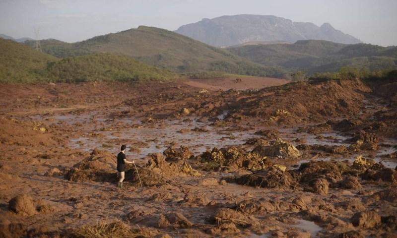 Um homem anda sobre o mar de lama no distrito de Bento Rodrigues após o rompimento de duas barragens Ricardo Moraes / REUTERS