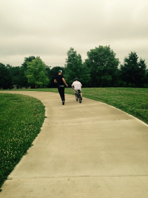 Youth at Adriel participated in a variety of activities during the summer. Above, an older teenage boy teaches one of the younger boys how to ride a bike.