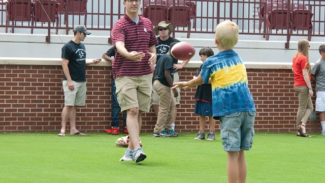 Mentor Ronnie Fields plays a little catch with his mentee Ray Chadwick, on Owen Field, waiting to meet Coach Bob Stoops during OU media day. (Mark Hancock)