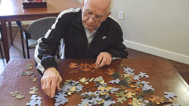 Residents at Prairie Winds Alzheimer's Special Care Center partake in daily rituals as part of Alzheimer's therapy like Bob shown working a puzzle.  mh
